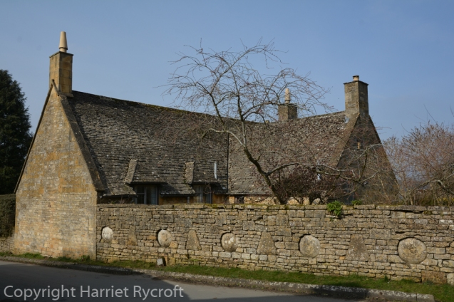 Staddle stones embedded in a handsome Cotswold stone wall in Snowshill